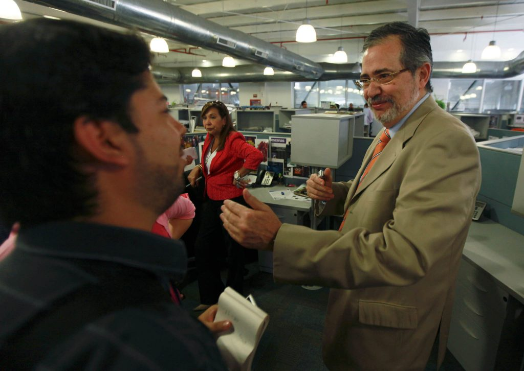 Man talking to people in newsroom (© Fernando Llano/AP Images)