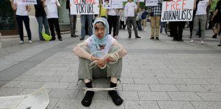 Demonstrators on a sidewalk protesting (© Francois Mori/AP Images)