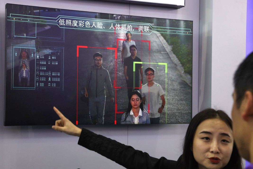 Woman pointing to a screen showing facial recognition software (© Ng Han Guan/AP Images)