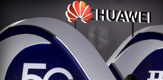 Huawei sign and person standing in front of it demonstrating equipment (© Mark Schiefelbein/AP Images)