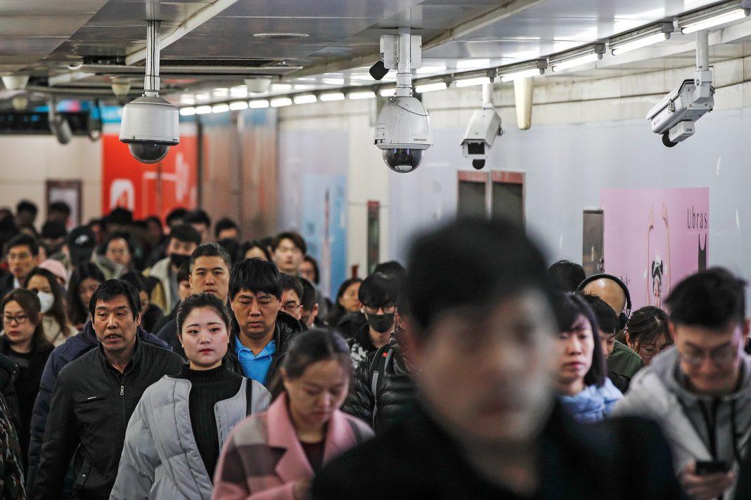 Multidão de pessoas andando sob câmeras de segurança (© Andy Wong/AP Images)