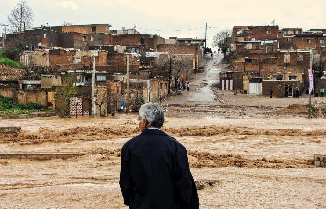 Un hombre observa una carretera inundada en un pueblo (© Erfan Keshvari/ISNA/AP Images)