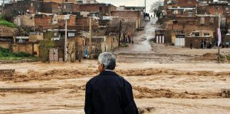 Man stands viewing flooded road in village (© Erfan Keshvari/ISNA/AP Images)
