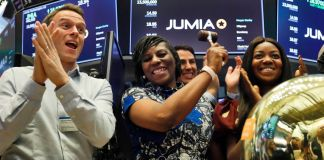 Smiling woman ringing the NYSE bell, surrounded by other smiling people (© Richard Drew/AP Images)