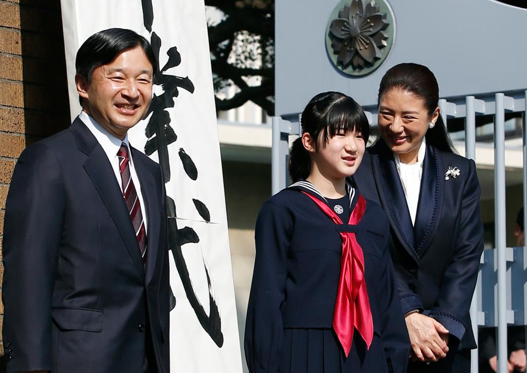 Teenage girl standing between parents (© Toru Hanai/AP Images)