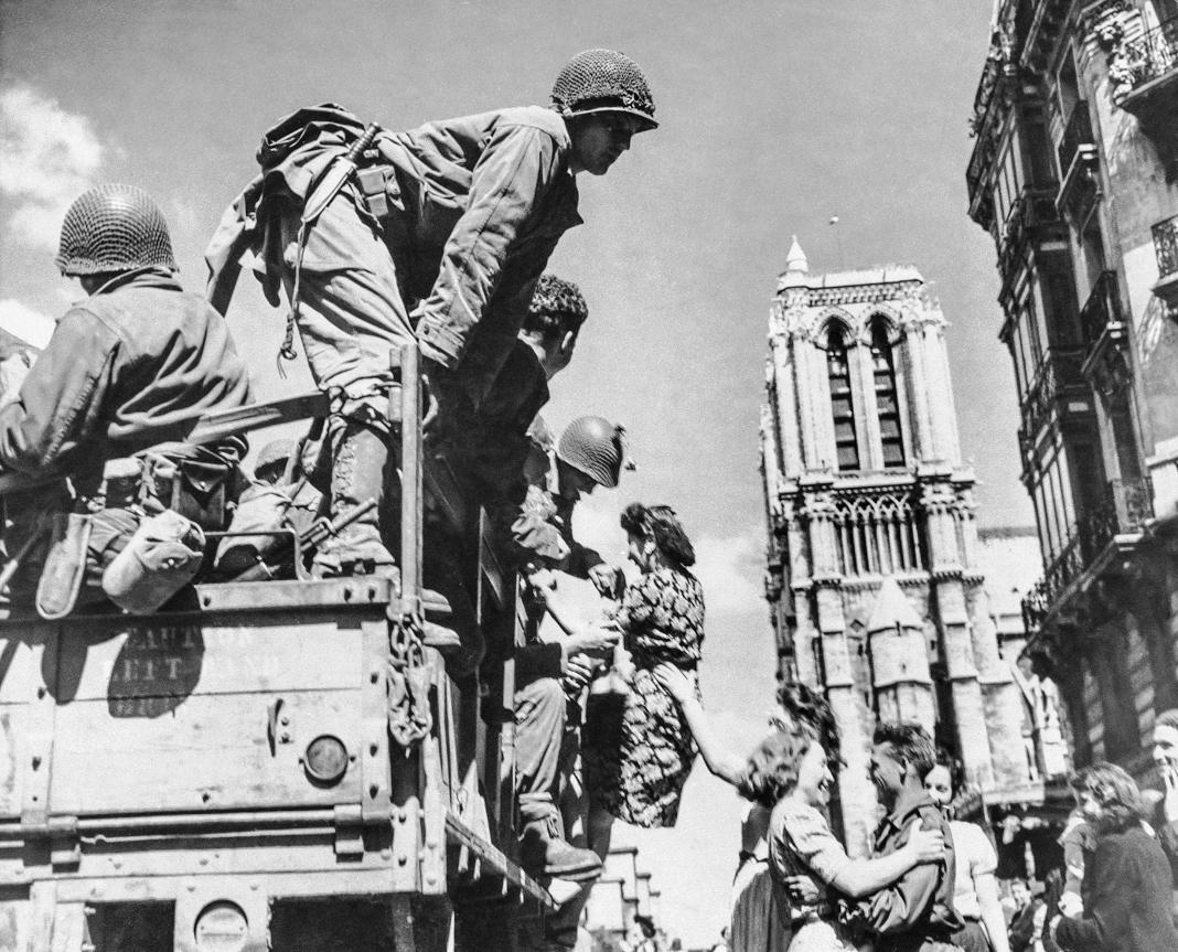 Soldados americanos sendo recebidos por mulheres francesas em frente à Catedral de Notre-Dame (© AP Images)