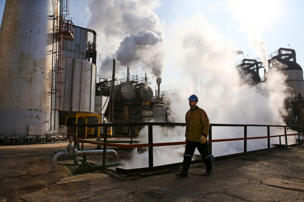 Man walking past oil refinery equipment (© Vahid Salemi/AP Images)