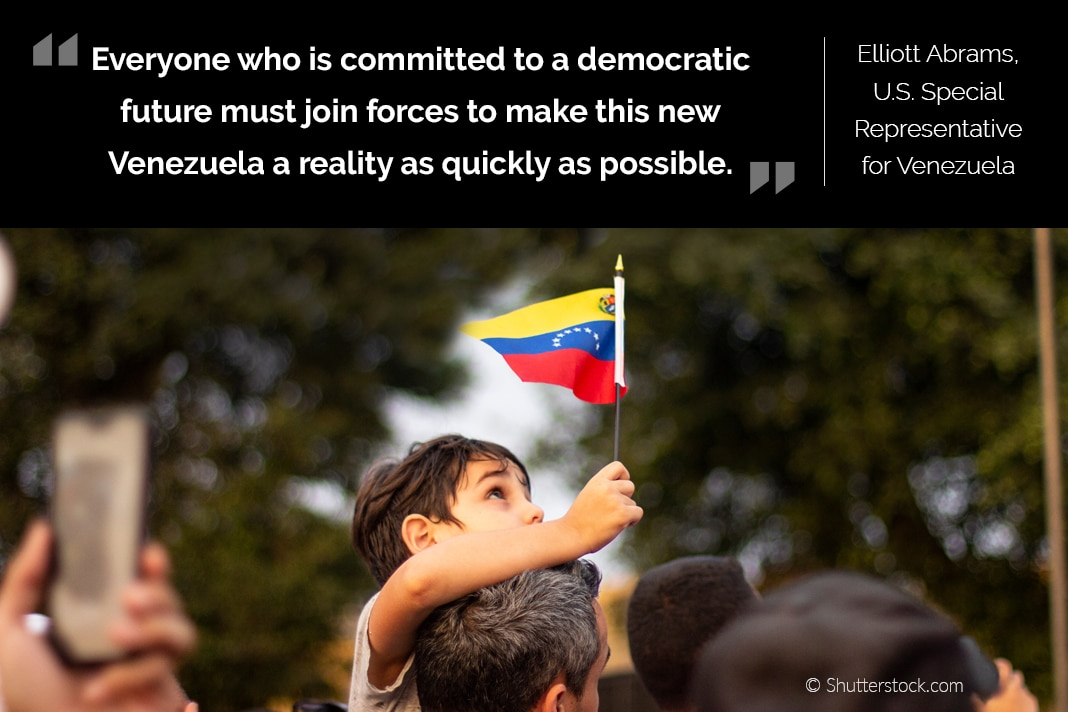 Photo of young boy held up in crowd raising small Venezuelan flag, with Abrams quote on top (State Dept./© Shutterstock.com)