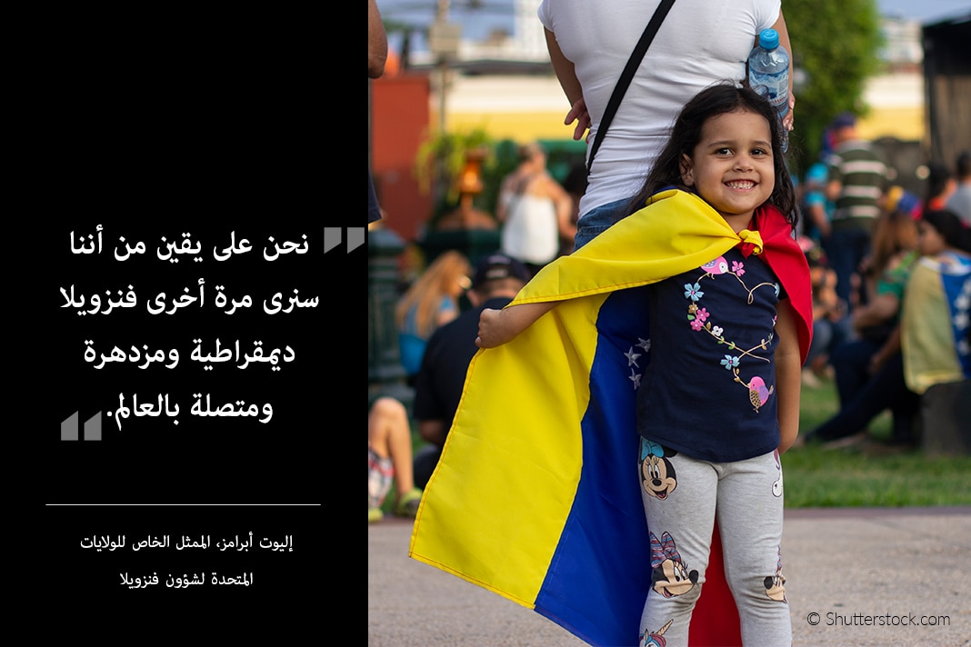 Photo of young girl wearing Venezuelan flag as cape leaning on adult, with Abrams quote at the side (State Dept./© Shutterstock.com)
