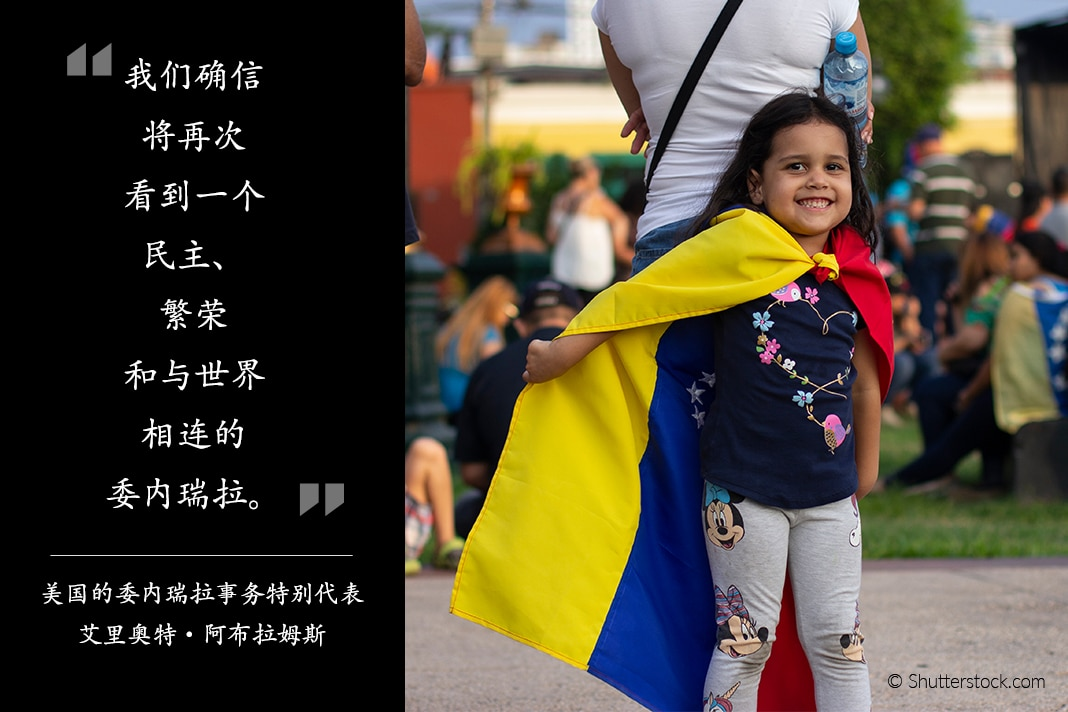 Photo of small girl leaning on adult, wearing Venezuelan flag as cape, with Abrams quote on the side (State Dept./© Shutterstock.com)
