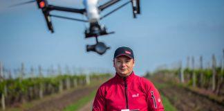 Un homme au milieu de vignes avec une télécommande dans les mains et un drone au-dessus de lui (Colby Gottert for USAID)
