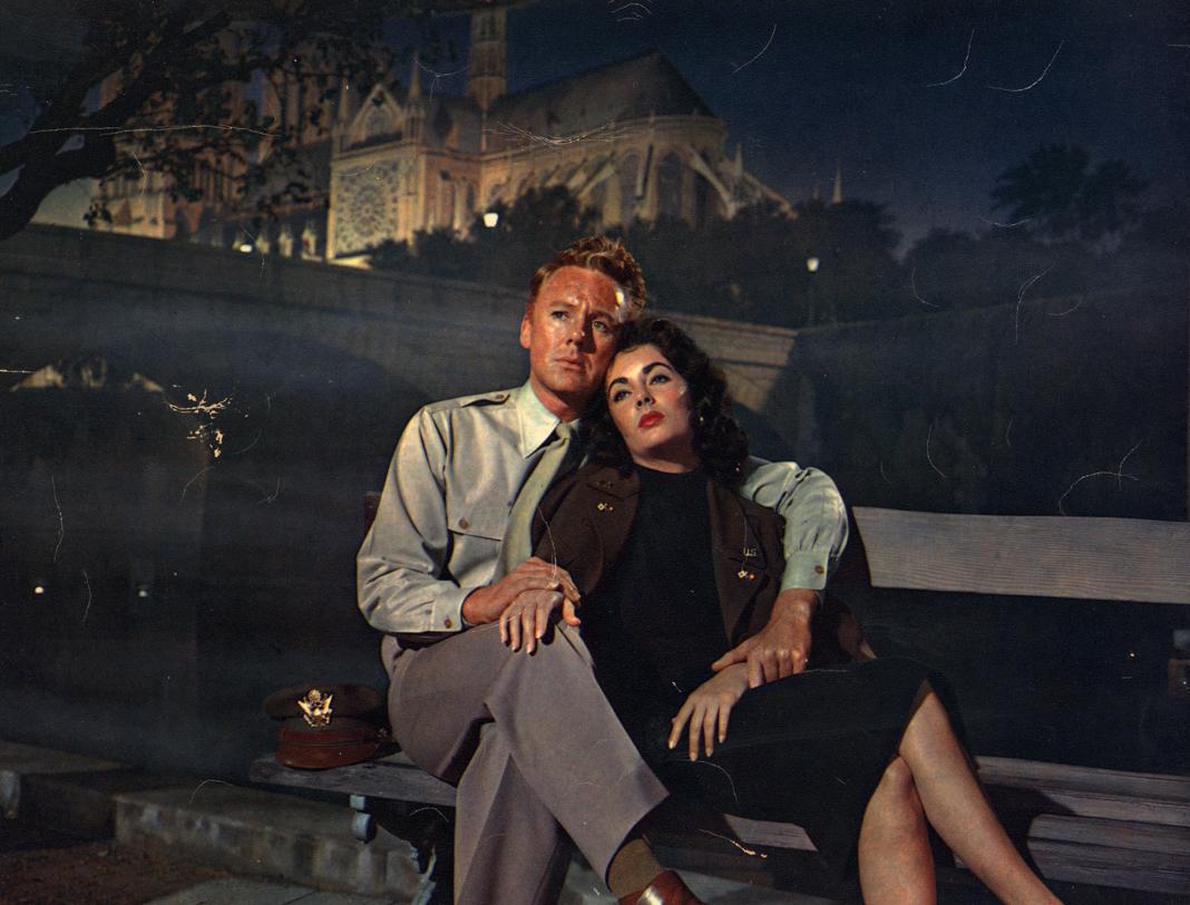 Atores Van Johnson e Elizabeth Taylor sentados em banco com a catedral ao fundo (© Hulton Archive/Getty Images)