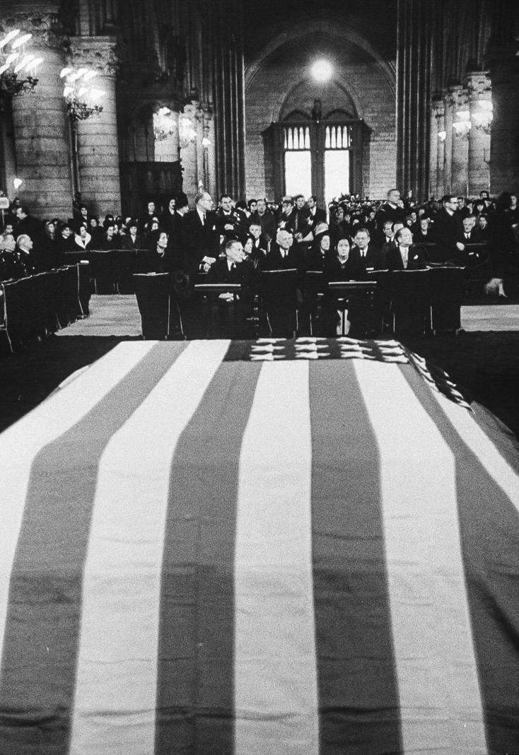 Caixão forrado com a bandeira dos EUA e pessoas sentadas na catedral (© Ralph Crane/Coleção The LIFE Picture/Getty Images)