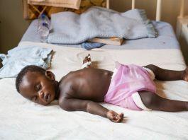 Baby sleeping on a bed (© Gideon Mendel/Corbis/Getty Images)
