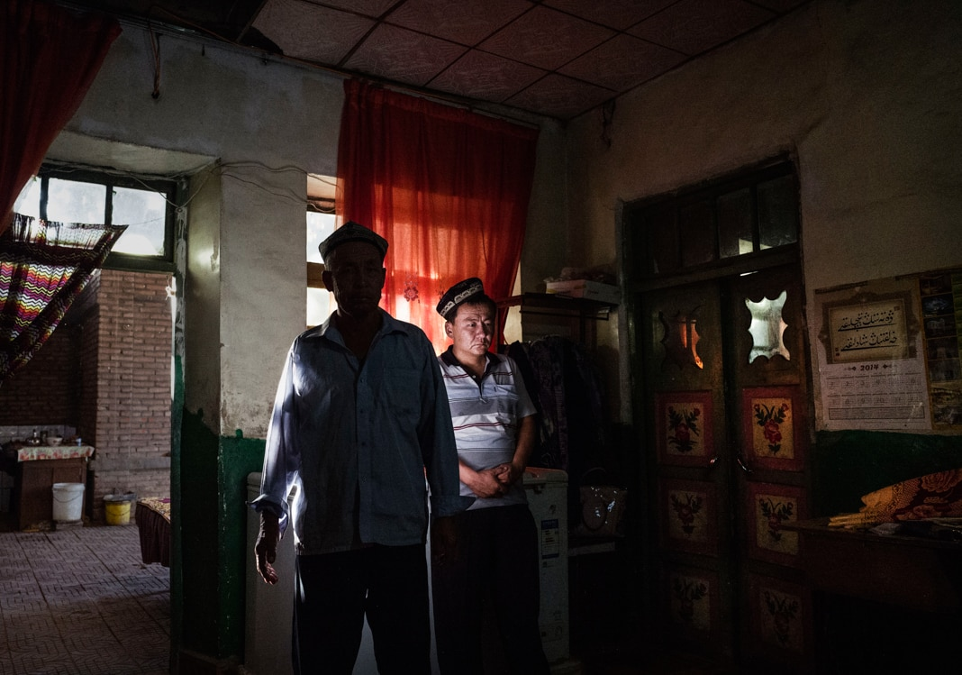Two men standing inside a shadowy home (© Kevin Frayer/Getty Images)