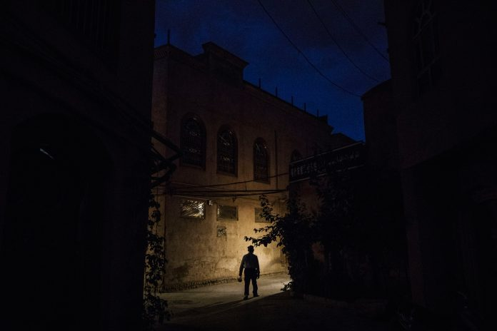 Lone figure walking along narrow street in darkness (© Kevin Frayer/Getty Images)
