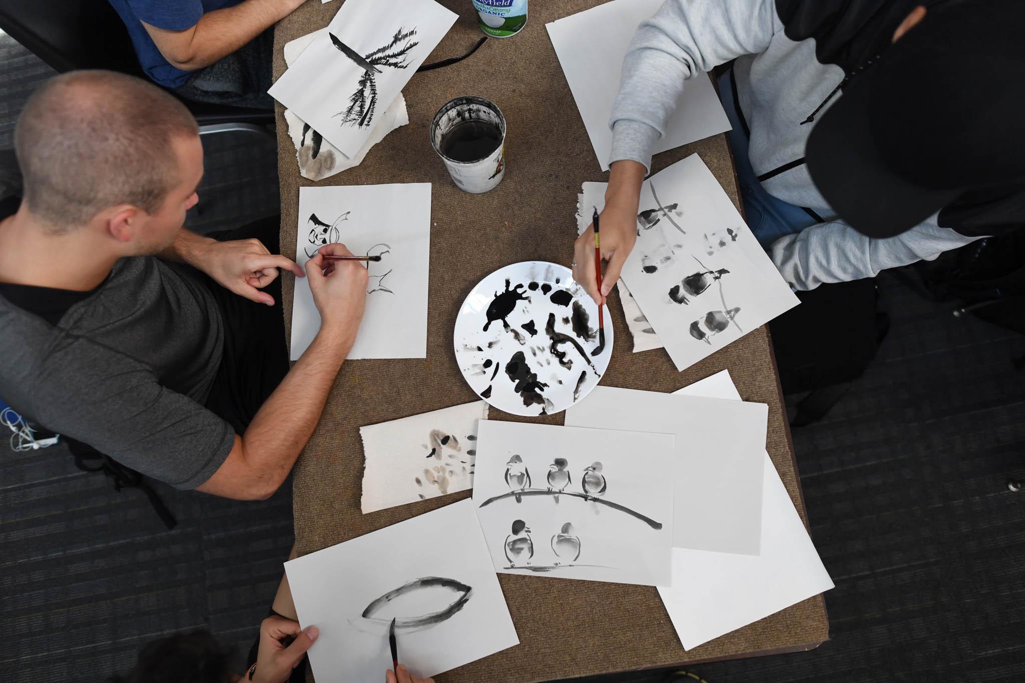Vue de haut d'une table sur laquelle des étudiants s'exercent à la peinture chinoise (© RJ Sangosti/The Denver Post/Getty Images)