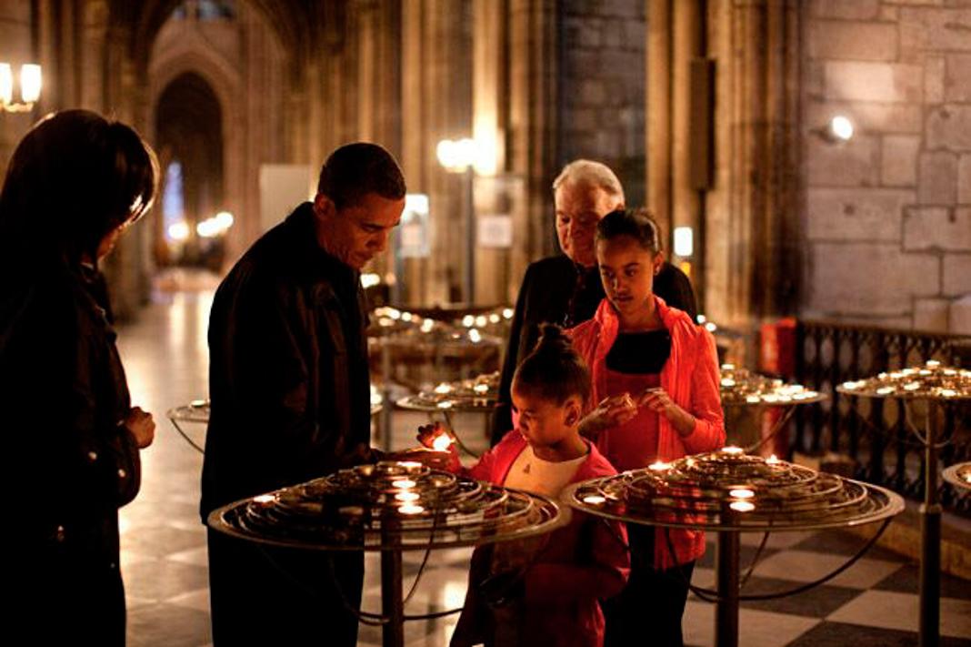 Barack Obama e a família acendem uma vela dentro da catedral; padre parado atrás observa (© Pete Souza/Casa Branca)