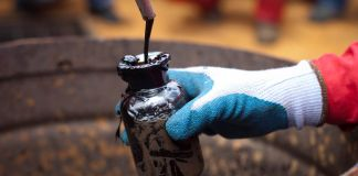 Gloved hand collecting oil in a small jar (© Carlos Garcia Rawlins/Reuters)