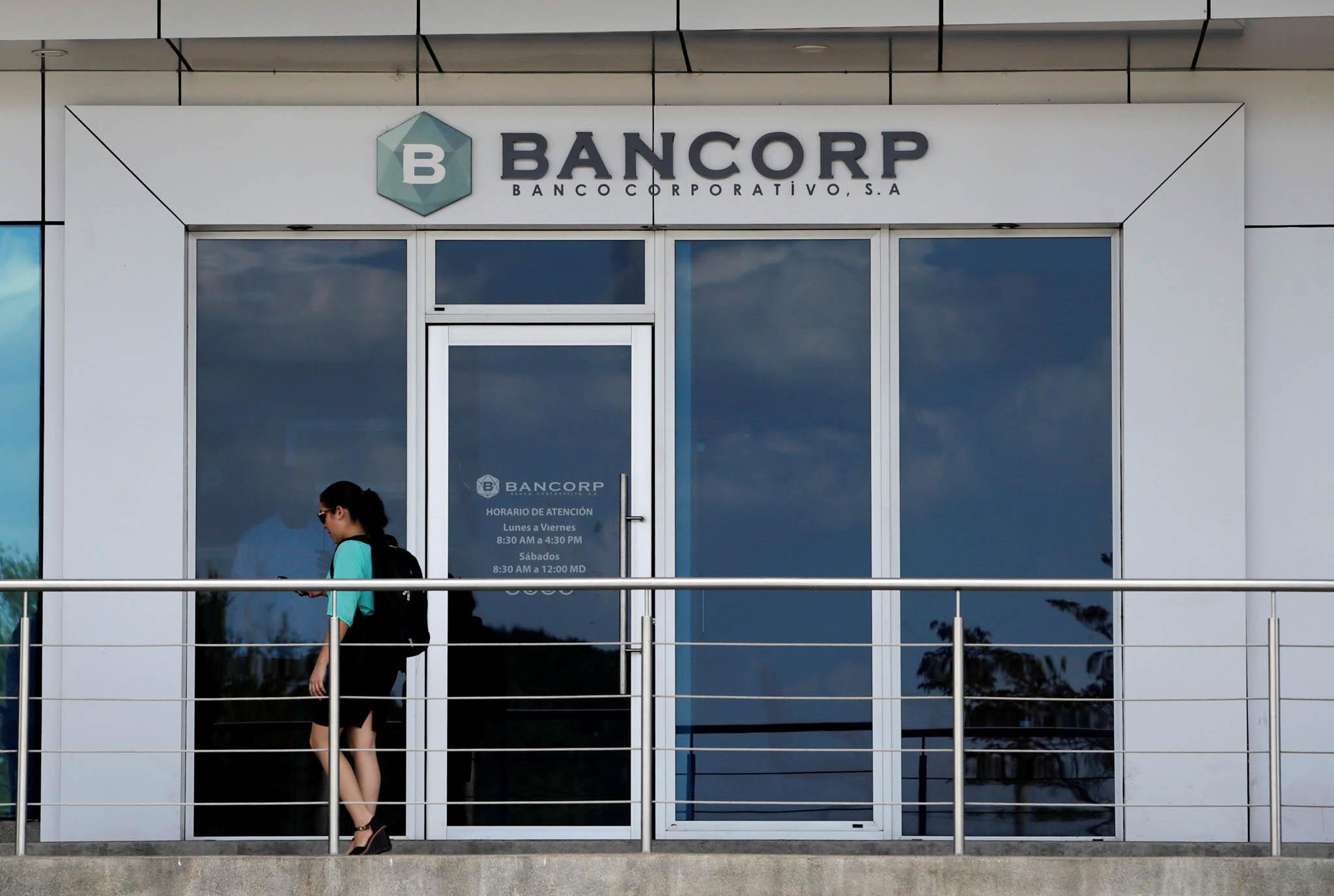 Une femme passant devant une devanture avec de grandes baies vitrées et une enseigne de la Bancorp. (© Oswaldo Rivas/Reuters)