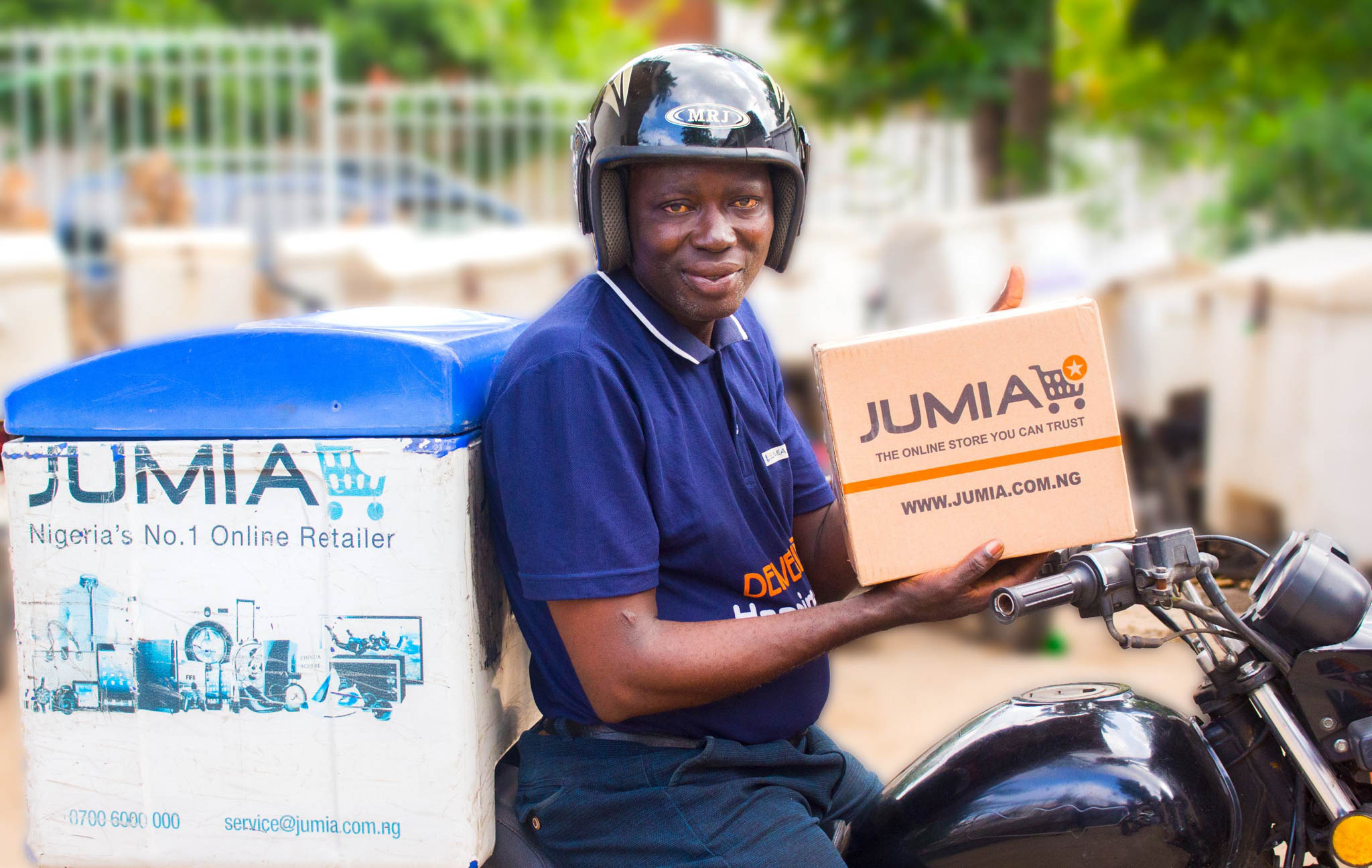 Man holding a parcel while seated on a motorbike (© Jumia)
