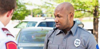 Police officer interrogating people at an emergency scene (State Dept.)