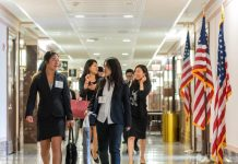 Women walking down a hallway with American flags on stands to their left (TOMODACHI Initiative)