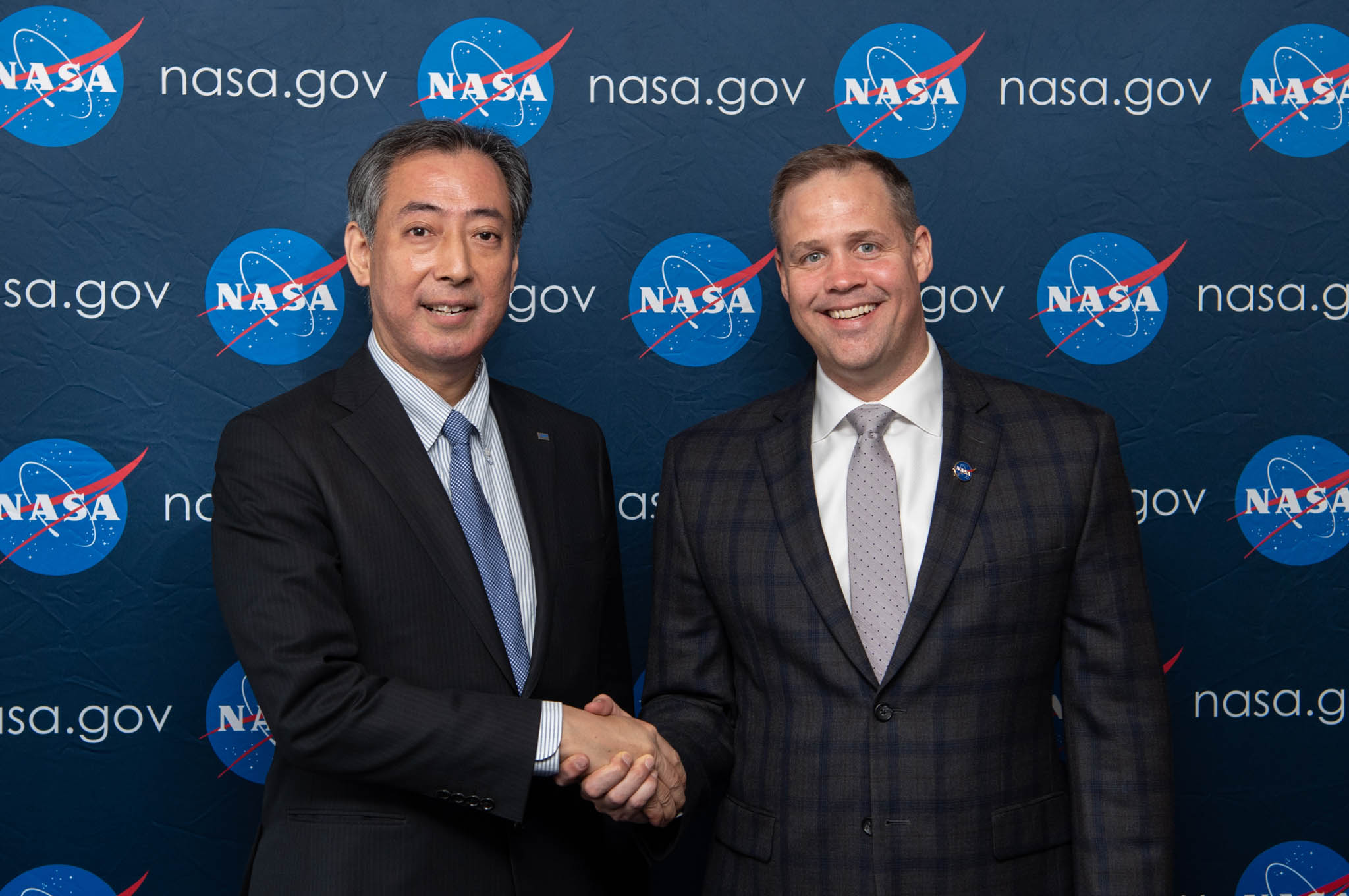 Two men shaking hands in front of wall with NASA signs (Aubrey Gemignani/NASA)