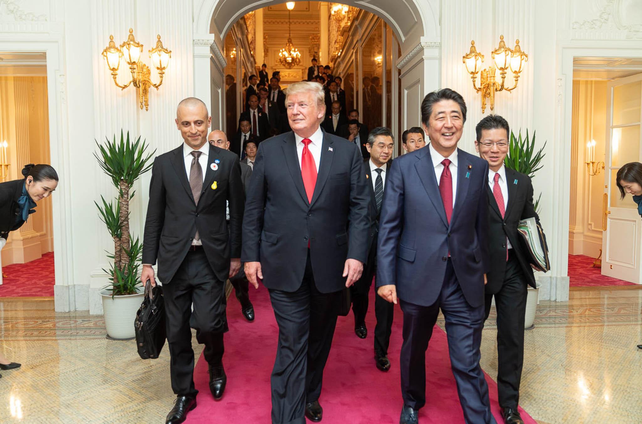 Donald Trump caminando con Shinzō Abe y otros (Shealah Craighead/La Casa Blanca)