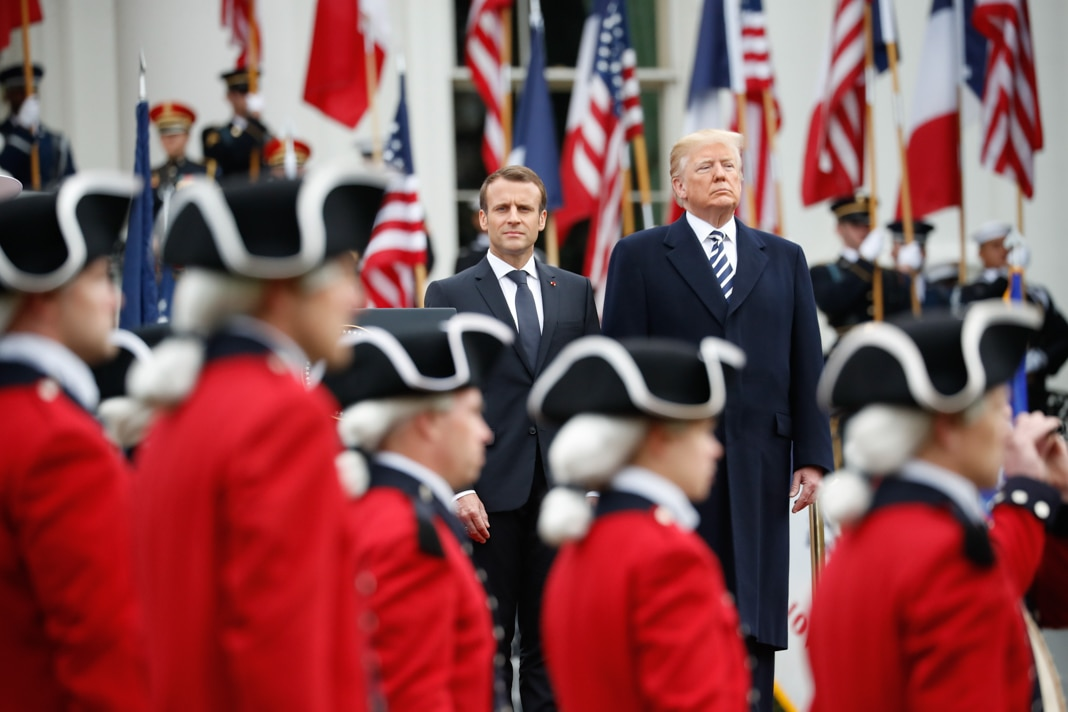 Macron and Trump standing at attention among uniformed service members (© Pablo Martinez Monsivais/AP Images)