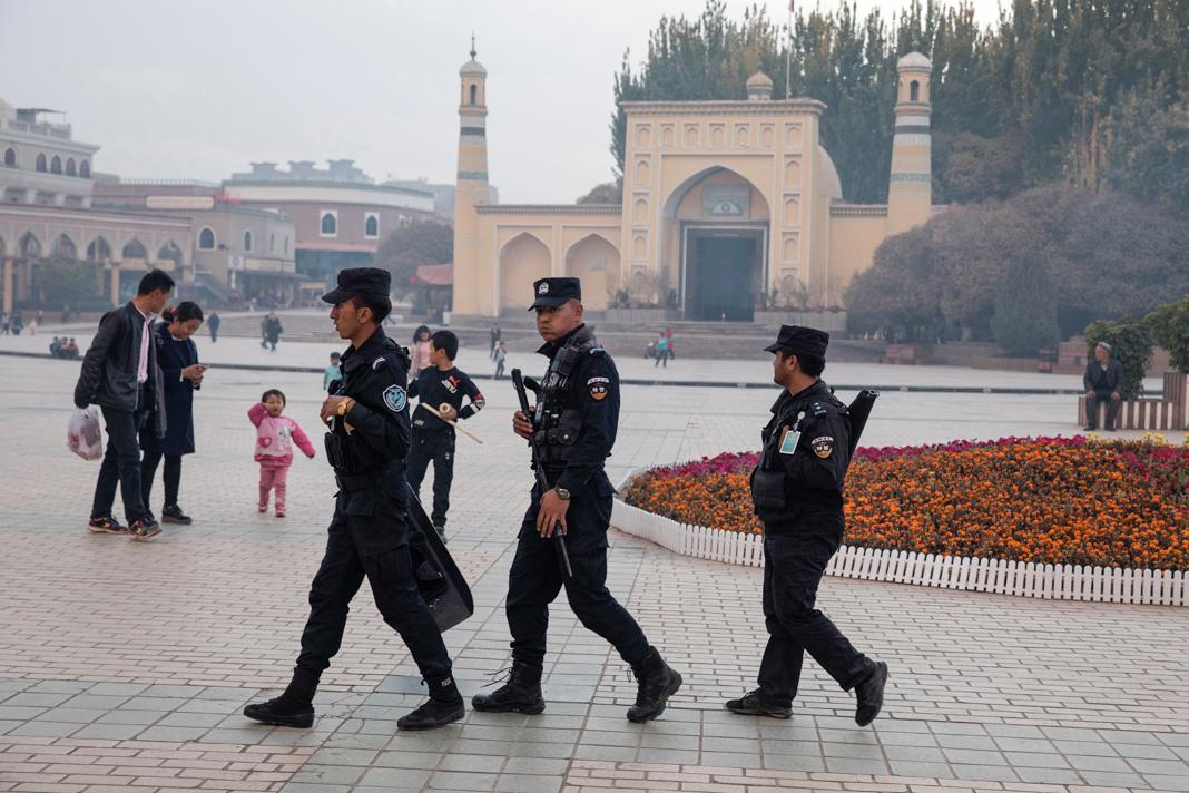 Pessoal de segurança uniformizado passando por uma mesquita (© Ng Han Guan/AP Images)
