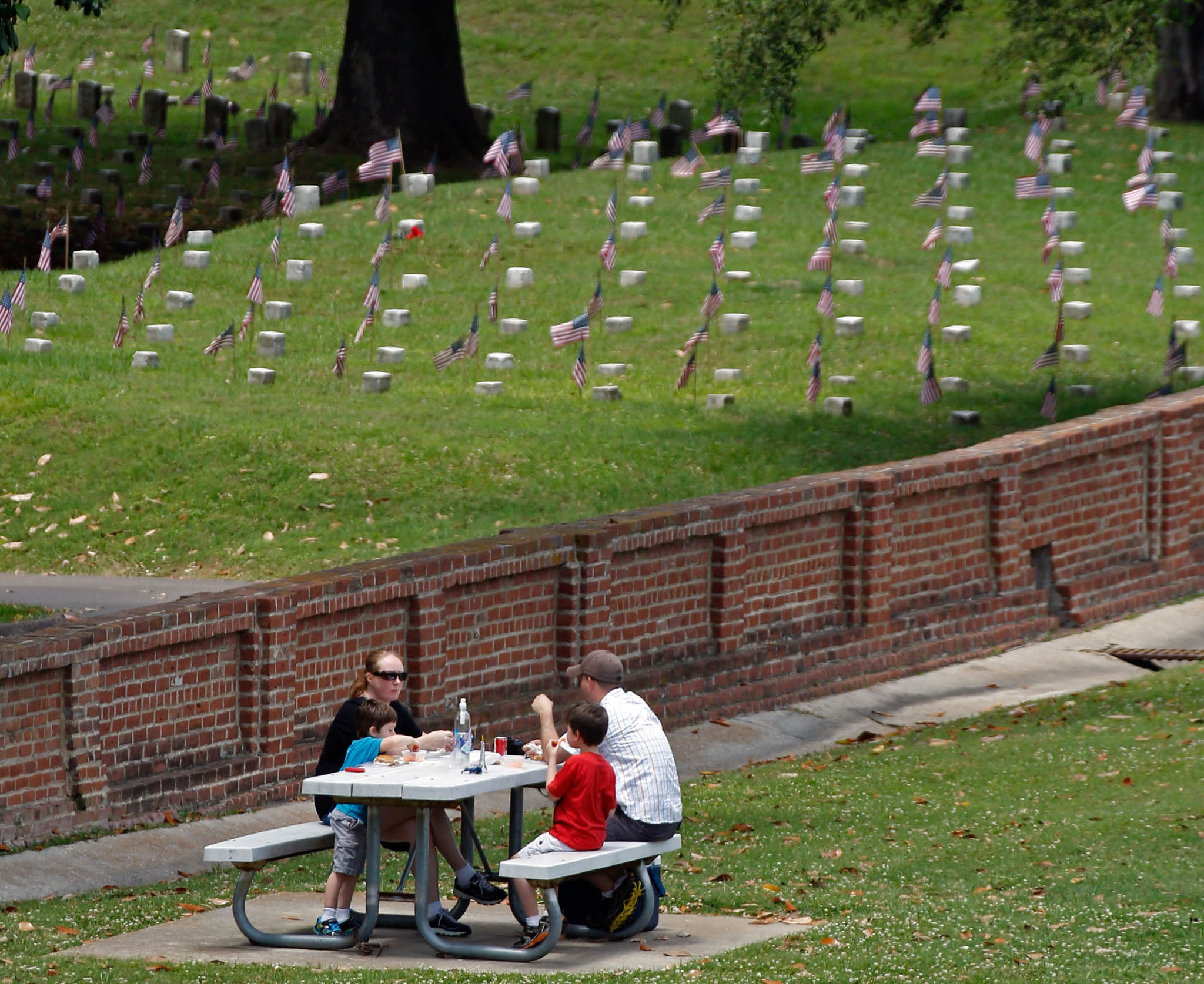 Family at picnic table near cemetery (© Rogelio V. Solis/AP Images)