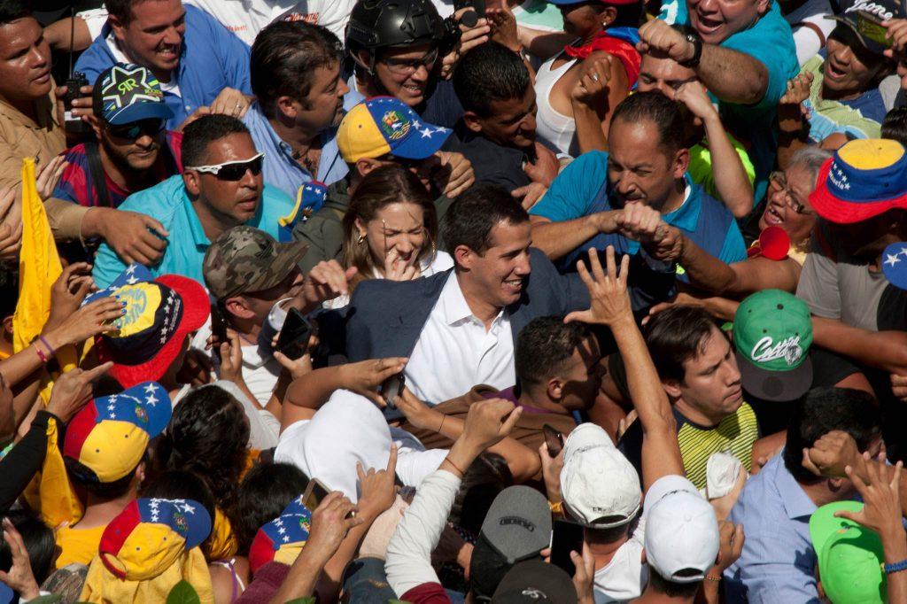 Juan Guaido walking in the center of a throng of people (© Juan Carlos Hernandez/AP Images)