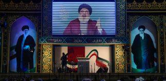 Voltada para uma tela gigante, plateia assiste a um vídeo com uma cena de um homem falando (© Hussein Malla/AP Images)