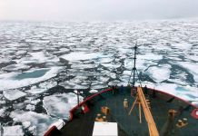 Ship floating in water filled with floating ice (© Devin Powell/NOAA/AP Images)
