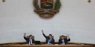 3 men seated, raising hands to vote under Venezuela government seal (© Fernando Llano/AP Images)