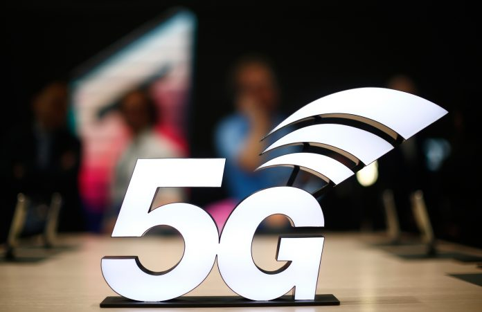 '5G' as a logo superimposed on blurry image of people (© Manu Fernandez/AP Images)