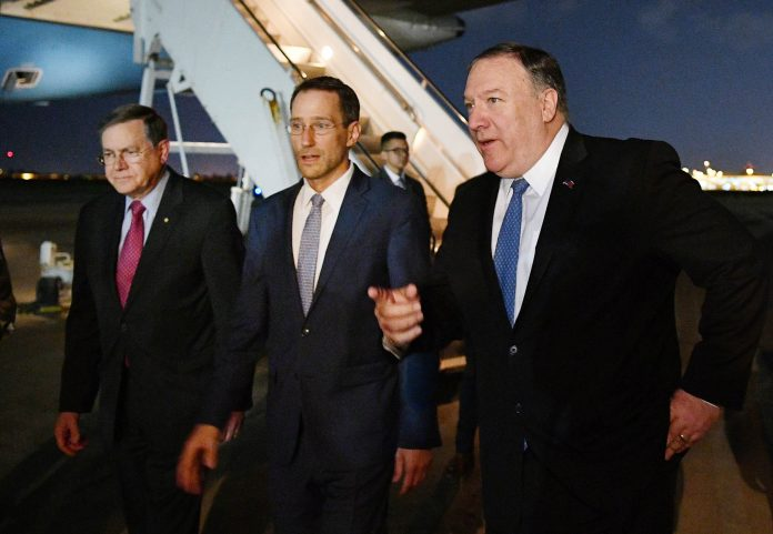 Mike Pompeo walking with other men on a tarmac at night (©Mandel Ngan/AP Images)
