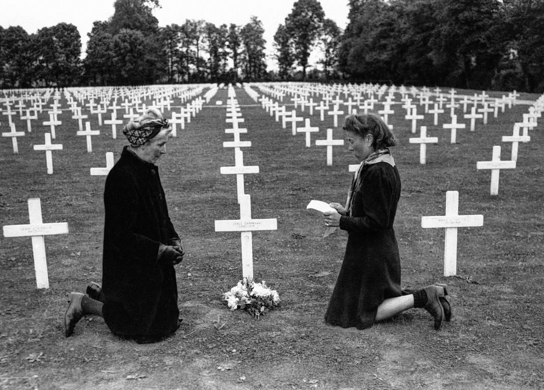 Two women kneeling among rows of white crosses (© AP Images)