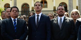 Three men standing at attention in front row of group of people (© Federico Parra/AFP/Getty Images)