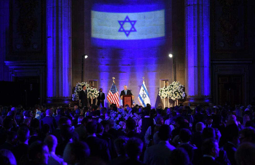Mike Pompeo delivering address under large Israeli flag. (© Mandel Ngan/AFP/Getty Images)