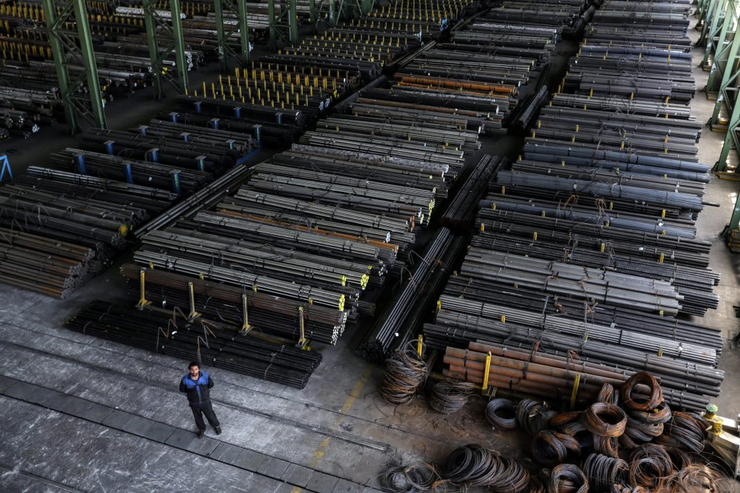 Man standing in metal factory (© Atta Kenare/AFP/Getty Images)
