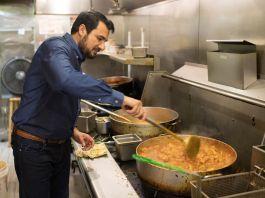 Kazi Mannan in restaurant kitchen stirring big pot (© Marvin Joseph/The Washington Post/Getty Images)