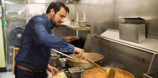Man in restaurant preparing food (© Marvin Joseph/The Washington Post/Getty Images)