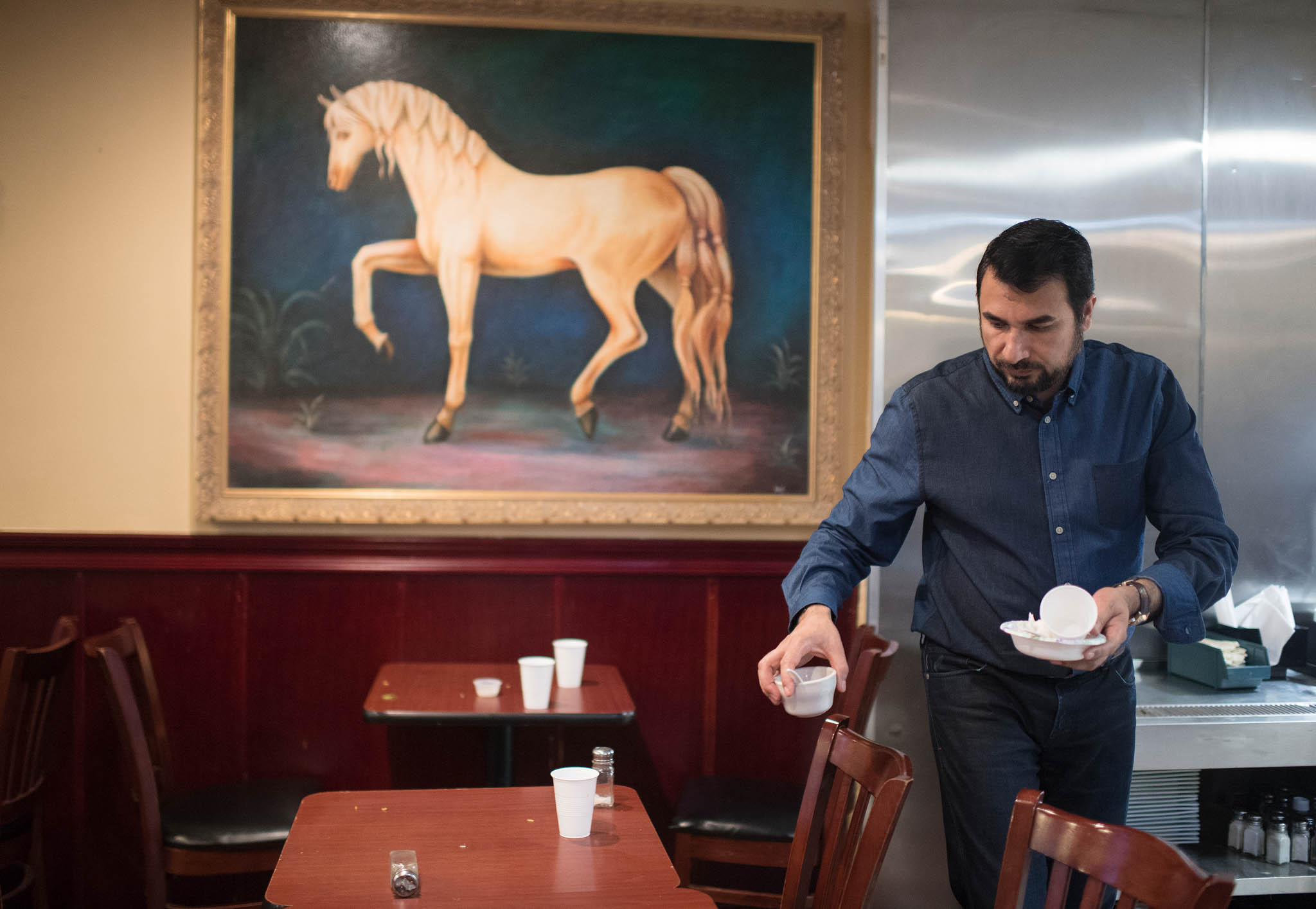 Kazi Mannan dans un restaurant, en train de débarrasser une table (© Marvin Joseph/The Washington Post/Getty Images)