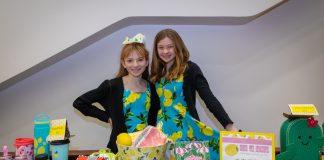 Duas meninas exibem as mercadorias de seu empreendimento em uma mesa (© Dia da Limonada)