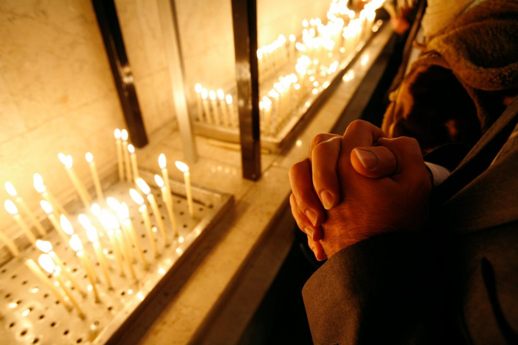 Lit candles and a person's hands clasped in prayer (© Morteza Nikoubazl/Reuters)
