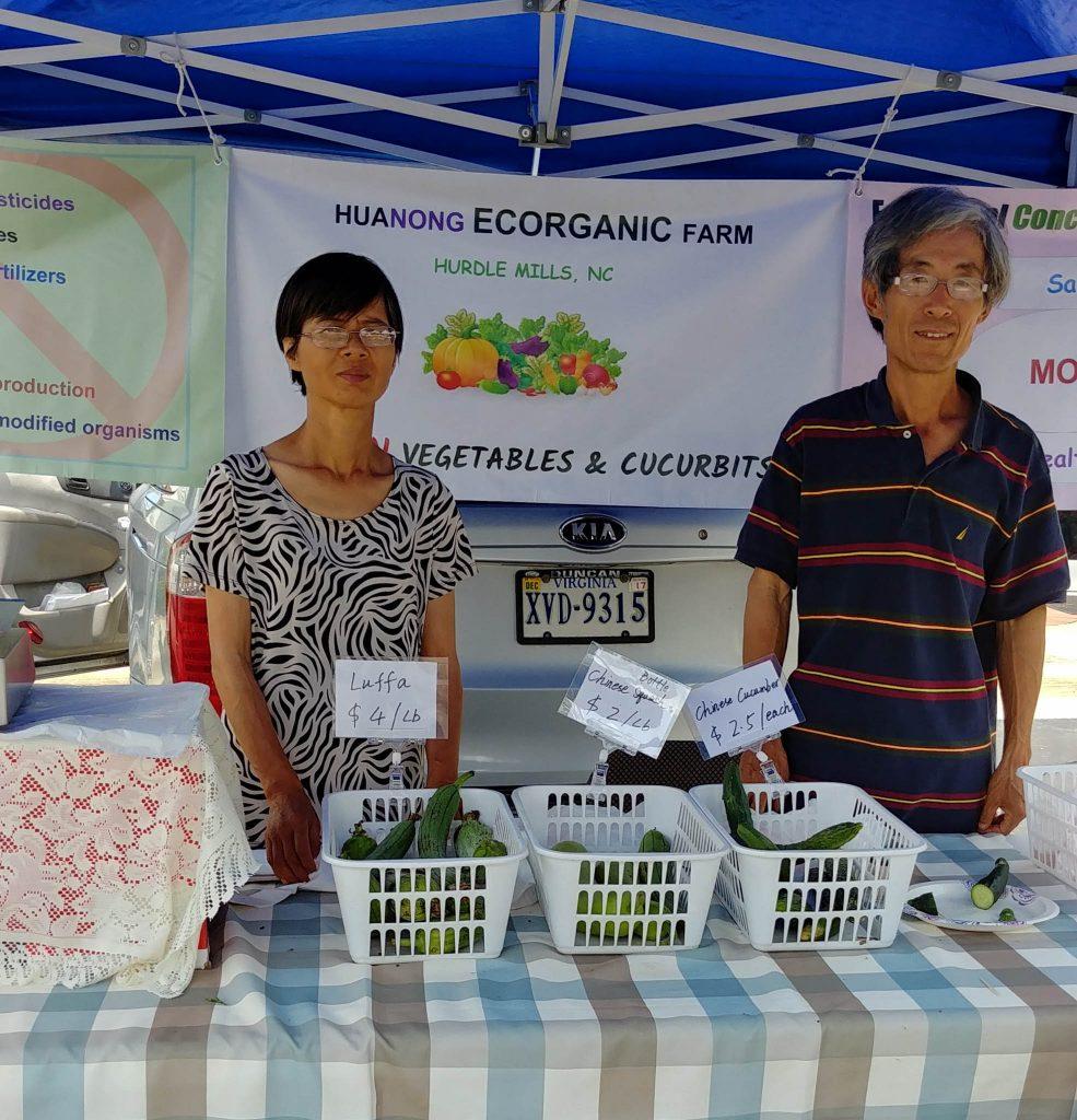 Hombre y mujer de pie en un puesto con cestas de productos agrícolas sobre una mesa (Foto cedida por Changhe Zhou)
