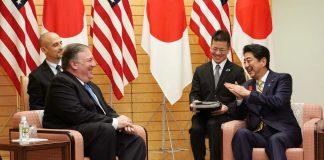 Quatro homens conversam sentados (© Eugene Hoshiko/AP Images)