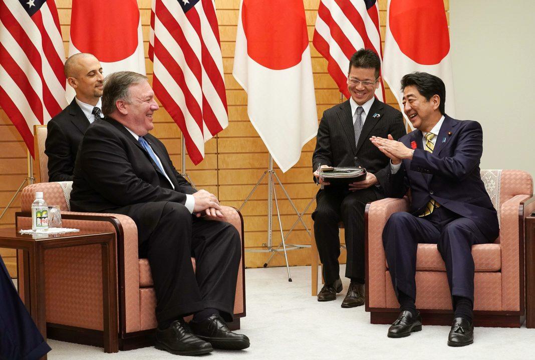 Quatre hommes assis en train de parler (© Eugene Hoshiko/AP Images)